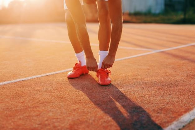 Закройте вверх sporty человека гнуть и связывая шнурок пока стоящ на суде в утре в лете.