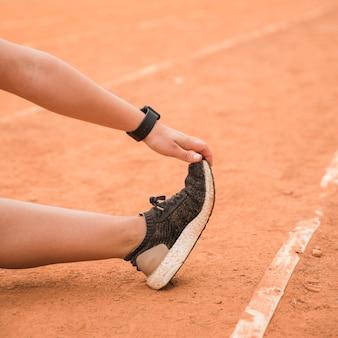 Крупным планом спортивный женщина, растяжения на стадионе трек
