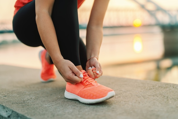 배경 다리에서 야외 무릎을 꿇 고 신발 끈을 묶는 스포티 한 여자의 닫습니다. 피트 니스 야외 개념입니다.