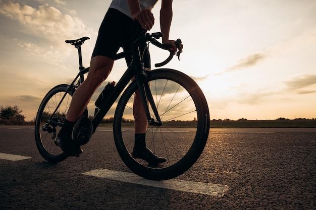 검은 자전거 도로에 서있는 강한 다리를 가진 스포티 한 젊은 남자의 닫습니다