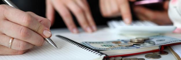 월별 모든 구매 및 비용을 기록하는 배우자의 확대. 소득 계산 및 저축 부부. 지폐와 동전 테이블에.