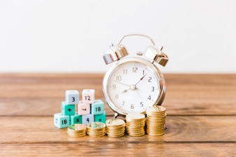Close-up of stacked coins in front of alarm clock and math blocks on wooden desk