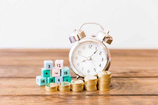 木製の机の上で目覚まし時計と数学のブロックの前に積み重ねられたコインのクローズアップ