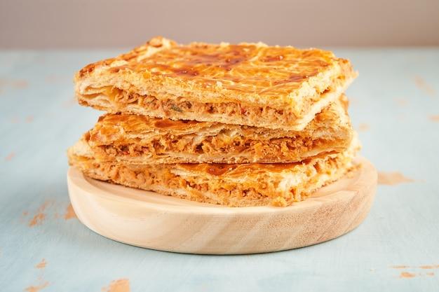 Закройте сложенные порции пирожка, фаршированного тунцом, на деревянной тарелке