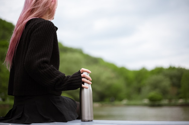 ピンクの髪の少女の手にステンレスボトルのクローズアップ。