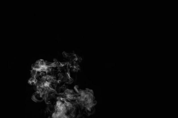 黒の背景に蒸気煙のクローズアップ。黒の背景、クローズアップに分離された白熱カーリースチーム煙。神秘的なハロウィーンの写真を作成します。抽象的な背景、デザイン要素
