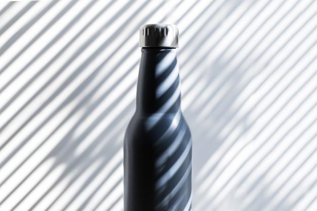 Крупный план стальной, экологической многоразовой термо-бутылки с водой на фоне теней в виде линий.