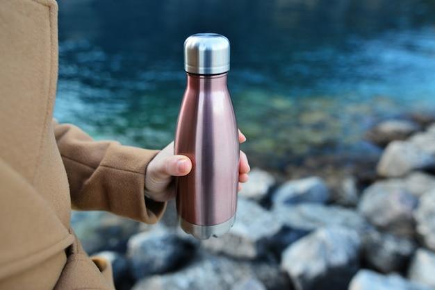 여성의 손에 강철 에코 열 물병의 클로즈업. 청록색 색조와 호수의 맑은 물 배경에 강철 열 물병.