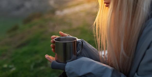 Susnet에서 젊은 금발 여자의 손에 뜨거운 음료와 강철 찻잔의 클로즈업.