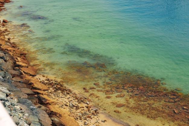 Крупный план камней и чистой воды на берегу пляжа