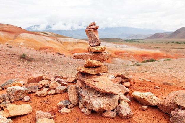 崖から落ちた石のクローズアップ。山や森を背景にしたピラミッド型のスタンド。灰色の石、背景のテクスチャ。