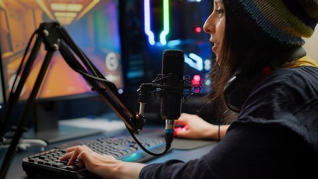 Rgb 키보드와 마우스를 사용하여 1인칭 슈팅 비디오 게임을 하는 스트리머의 클로즈업. 게임 스튜디오에서 늦은 밤 e스포츠 토너먼트 동안 다른 플레이어와 스트리밍 채팅에 대해 이야기하는 게이머