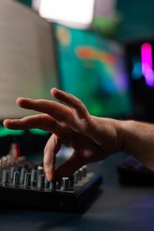 Крупный план стримера, использующего звук микшера в игровой домашней студии для онлайн-соревнований с друзьями на профессиональном мощном пк
