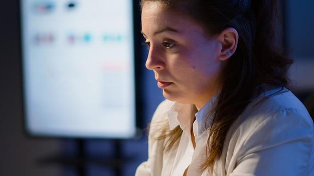 노트북 앞에서 초과 근무를 하는 스타트업 사무실의 직장에 앉아 피곤한 눈을 마사지하는 스트레스를 받는 매니저 여성의 클로즈업. 마감일을 존중하기 위해 과로하는 사업가.