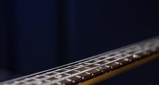 흐릿한 검정색 배경 복사 공간에서 베이스 기타의 현을 닫습니다.