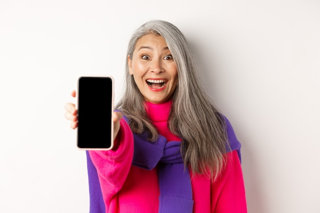 Закройте вверх стильной азиатской старшей женщины протягивая руку с мобильным телефоном, показывая пустой экран смартфона и усмехаясь, стоя на белизне.