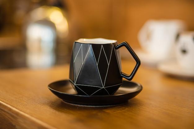 Крупный план стильной черной кружки на блюдце с ароматным чаем или кофе на деревянной столешнице в кафе или дома. утренний рутинный напиток.
