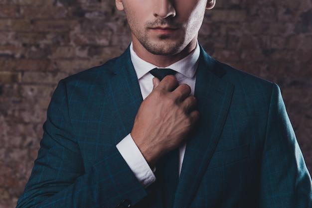 ネクタイを修正する黒のスーツでスタイリッシュな男のクローズアップ