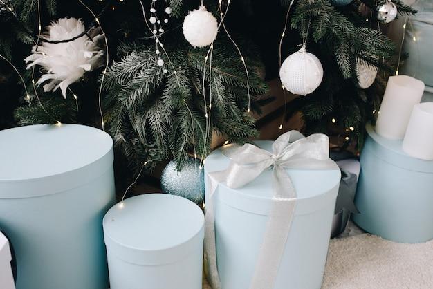 Крупным планом стильно упакованные рождественские подарки рядом с красиво украшенной елкой