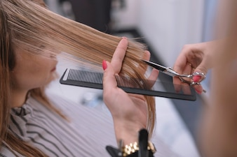 Close-up of stylist cutting hair ends