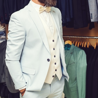 슈트의 클로즈업입니다. 상점에서 정장 행에 대 한 고전적인 조끼에 수염을 가진 사업가. 밝은 파란색 천 재킷에 수염이 있는 세련된 남자. 쇼룸에서 옷을 입어보고 포즈를 취하고 있습니다. 광고 사진
