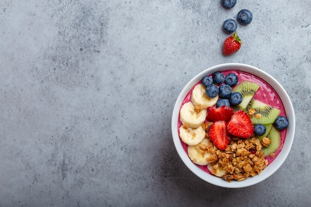 회색 콘크리트 배경에 딸기, 바나나, 블루베리, 키위 과일, 그래놀라를 넣은 여름 아사이 스무디 그릇을 클로즈업합니다. 과일과 시리얼이 포함된 조식 그릇, 위쪽 전망, 텍스트 공간