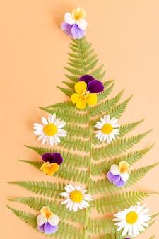 팬지와 카모마일 꽃으로 장식된 고사리로 만든 여름 크리스마스 트리를 닫습니다. 축제 인사말 카드, 에코 개념입니다.