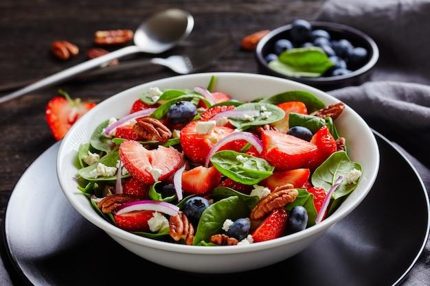 暗い木製のテーブル、上からの風景、マクロの白いボウルにイチゴ、ブルーベリー、ほうれん草、ピーカンナッツ、砕いたフェタチーズの夏のサラダのクローズアップ