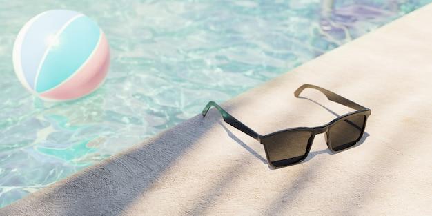 焦点が合っていない背景に水とボールとプールの端にサングラスのクローズアップ