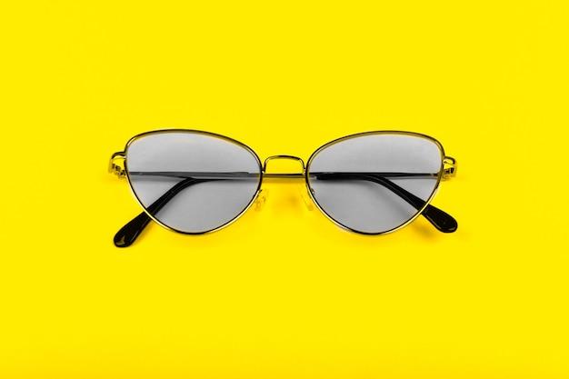 Крупный план солнцезащитных очков на желтом фоне. модные цвета концепции 2021 года.