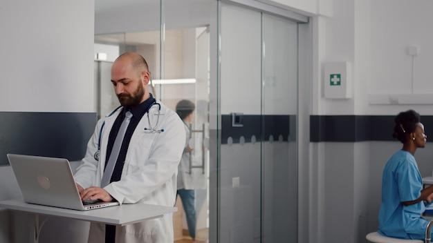 医療ユニフォームタイピング回復治療を身に着けている外科医の医師のクローズアップ