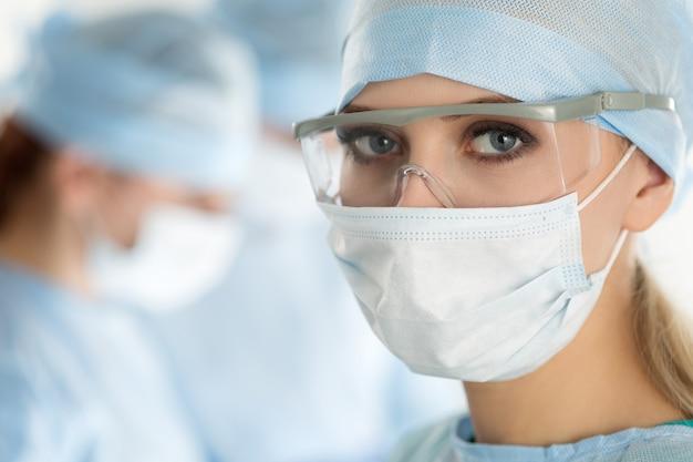 手術室で実行する同僚と探している外科医の女性のクローズアップ