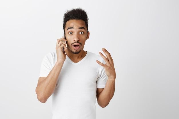電話で話している驚きのアフリカ系アメリカ人の男のクローズアップと驚いて見える