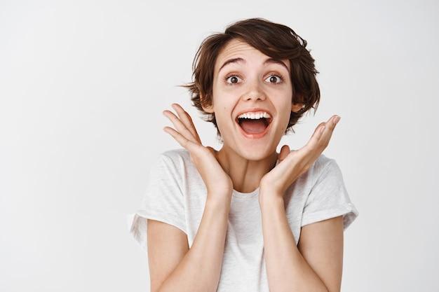 びっくりした、びっくりした、魅了されたように見える、白い壁を言って驚いてあえぎながら驚いて幸せな女性のクローズアップ