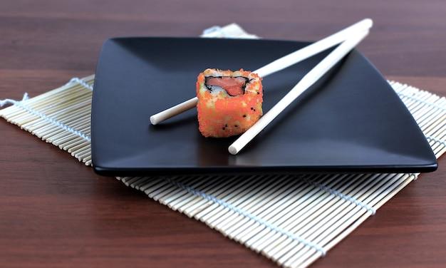 木製のテーブルに寿司と箸のクローズアップ。コピースペース付きの写真
