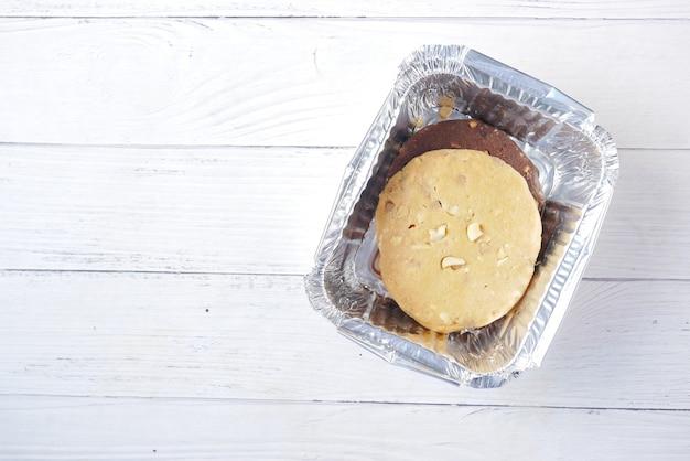 나무 테이블에 있는 테이크 아웃 상자에 달콤한 쿠키를 닫습니다