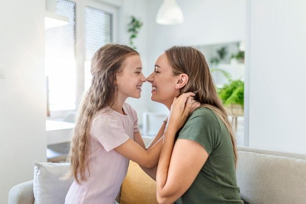 彼女の若い母親と抱きしめる甘いかわいい娘のクローズアップ。自宅のソファでかわいい娘を抱きしめる素敵な母親。