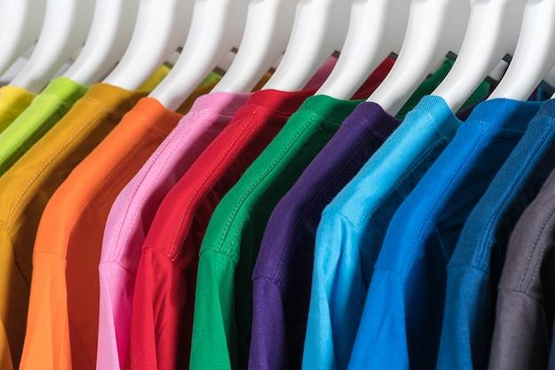 Крупным планом футболки, одежда на вешалках на белом фоне