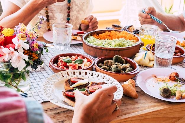 一緒に食べる人々のグループと新鮮なベジタリアン料理でいっぱいのテーブルのクローズアップ