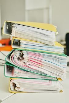 オフィスでの粘着メモが添付されたファイルでいっぱいのカラフルなフォルダのスタックとテーブルのクローズアップ