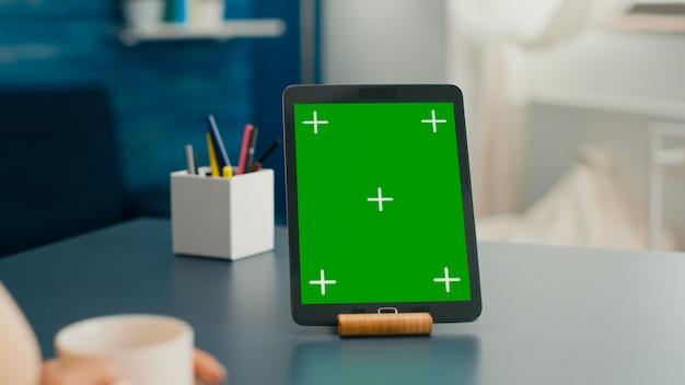 사무용으로 사용되는 모의 녹색 화면 크로마 키 디스플레이가 있는 태블릿 컴퓨터를 닫습니다. 책상에 앉아 있는 격리된 가제트를 사용하여 커뮤니케이션 프로젝트에서 일하는 프리랜서 여성