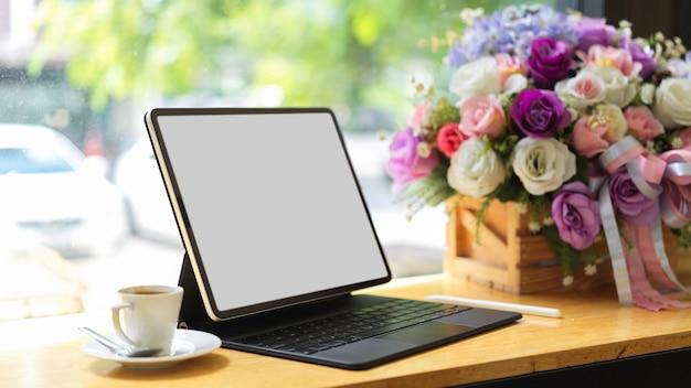 Закройте макет планшета с пустой экранной клавиатурой и украшением на деревянном столе в кафе