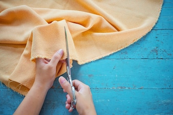 Close up of tailor's hand cutting a fabric on blue wooden table