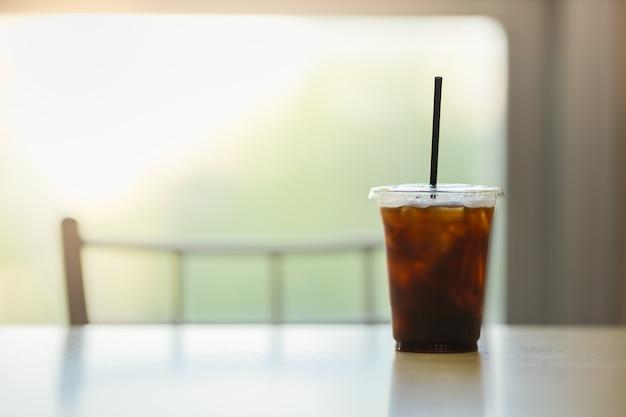가까이 복사 sapce 테이블에 레스토랑에서 아이스 블랙 커피 (아메리카노)의 플라스틱 컵을 빼앗아