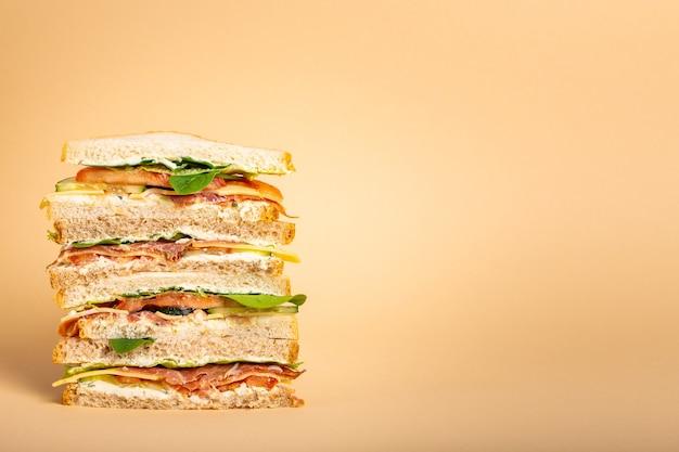 パステルイエローの背景にチーズ、ハム、生ハム、新鮮なレタス、トマト、きゅうりと背の高いカットのおいしいサンドイッチのクローズアップ。朝食やランチにヘルシーなグルメサンドイッチ。テキスト用のスペース