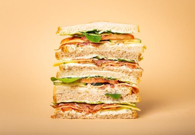 パステルイエローの背景にチーズ、ハム、生ハム、新鮮なレタス、トマト、きゅうりと背の高いカットのおいしいサンドイッチのクローズアップ。朝食やランチにヘルシーなグルメサンドイッチ