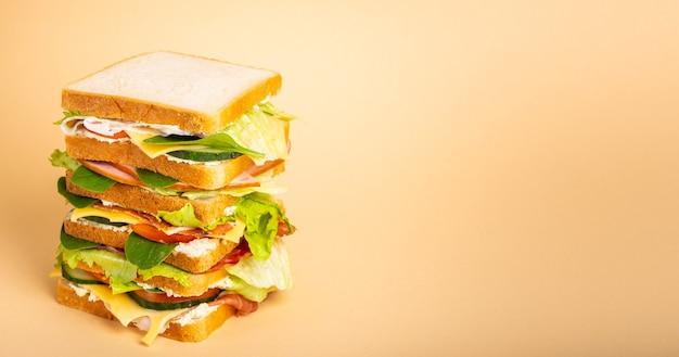 パステルイエローの背景にチーズ、ハム、生ハム、新鮮なレタス、トマト、きゅうりと背の高い全体のおいしいサンドイッチのクローズアップ。朝食やランチにヘルシーなグルメサンドイッチ。テキスト用のスペース