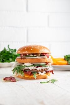Крупный план вкусного бургера на светлом деревянном кирпичной стене