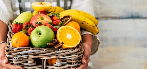 女性の手とコピースペースの背景によって保持されているおいしい新鮮な果物のバケツのクローズアップ-ダイエット健康的なライフスタイルの概念のためのカラフルな季節の食べ物