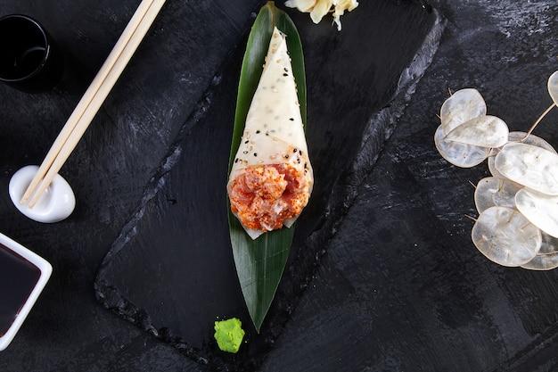 Крупным планом вкусные суши ролл руки в mamenori с тунцом и икрой тобико, подается на темной каменной плите с соевым соусом и имбирем.
